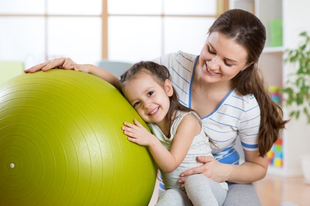 child ball: Cute kid girl  and mother with fitness ball at home Stock Photo