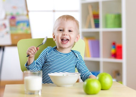 baby eating: Child boy eating cereal or cheese with the milk in nursery