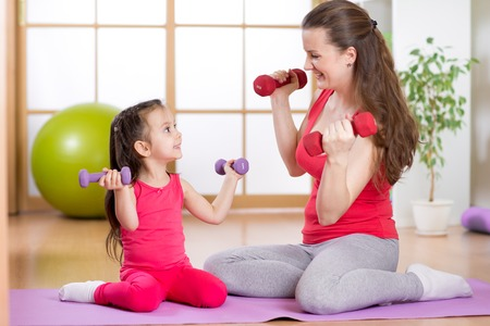 Woman and child daughter doing fitness exercises  with dumbbells