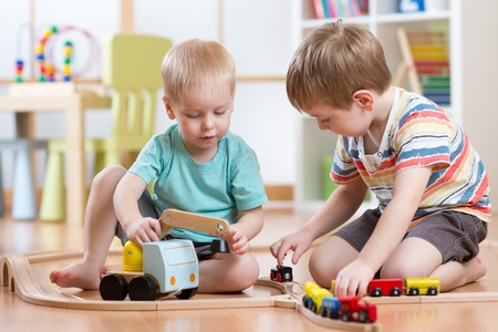 brothers: Children boys playing railroad together in playroom