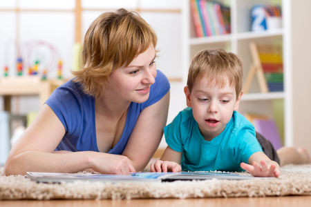 read magazine: mom and son reading book on carpet in room Stock Photo