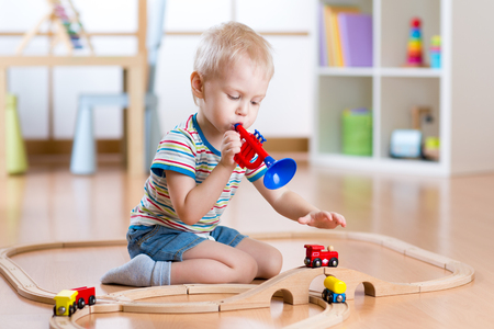 kids toys: Little boy playing with wooden railway on the floor in nursery Stock Photo