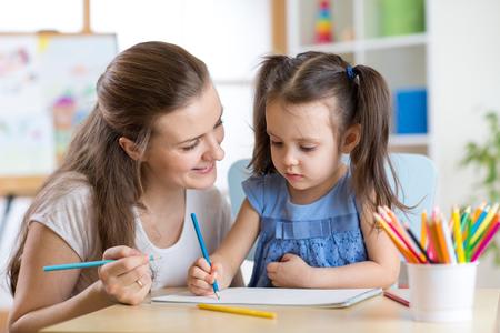 maestra preescolar: Madre joven mirando cómo su hija niño hacer un dibujo