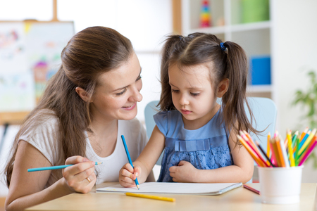 kindergarten teacher: Young mother looking how her child daughter drawing a picture