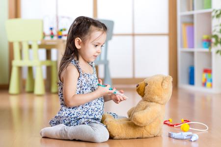 paediatrics: kid girl playing a doctor on floor in children room