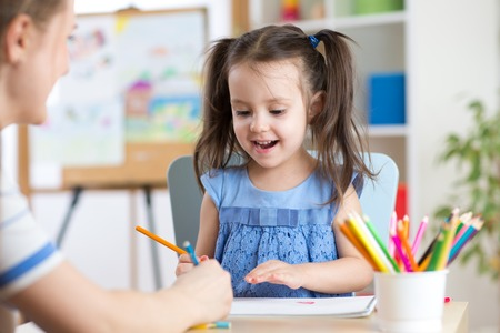 teaching crayons: Woman helping her child daughter with homework