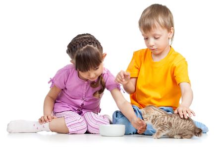 homeless children: children - boy and girl feeding homeless cat kitten Stock Photo