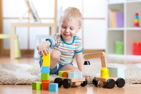 Child is happy to play toy building blocks and loader car