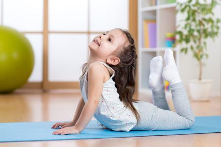 jong geitjemeisje die gymnastiek op mat thuis doen Stockfoto