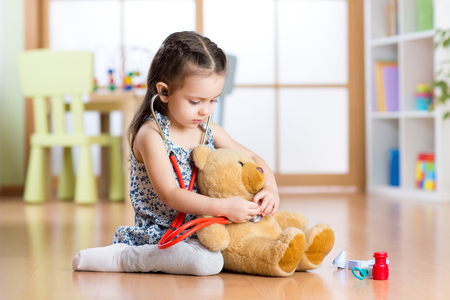 Adorable child girl with stethoscope and teddy bear sitting on floor, on home interior background