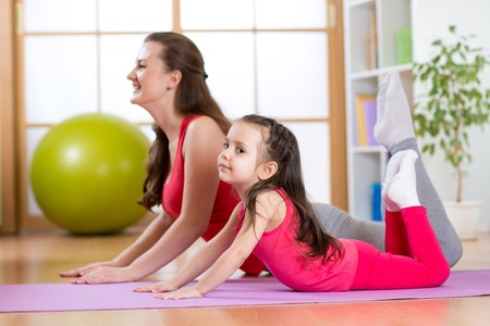 mum and daughter: Healthy life education. Mother and child girl exercising together Stock Photo