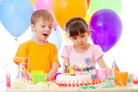 3 4 years: Happy children looking at birthday cake over festive background Stock Photo