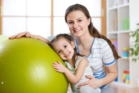 large ball: Cute child girl  and mother with fitness ball at home