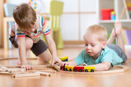 children at play: Cute children playing with wooden train. Toddler kids playing with blocks and trains. Boys building toy railroad at home or daycare. Educational toys for preschool and kindergarten child. Stock Photo