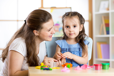 little dough: Mother and child daughter at home molded from clay and play together. Concept of school or home education.