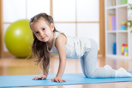 kid girl doing gymnastics or yoga in nursery