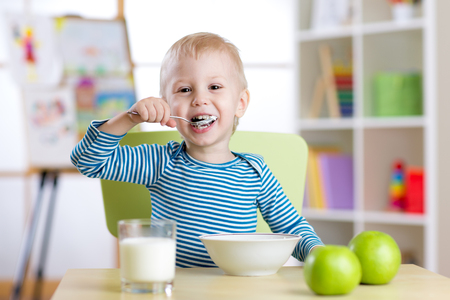 hungry children: kid eats healthy food at home or kindergarten