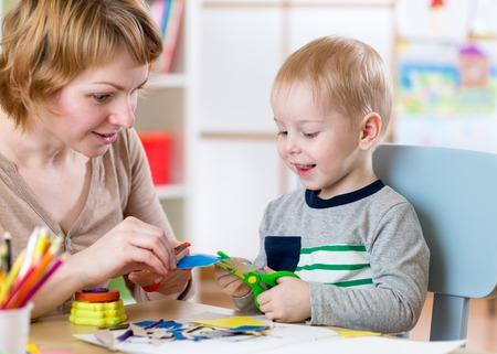 scissor: Woman teaches kid boy handcraft at kindergarten or playschool or home. Child with scissors cut paper in play room. Preschool.