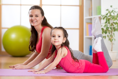 synchronously: Mom and child daughter do gymnastics. Family sports