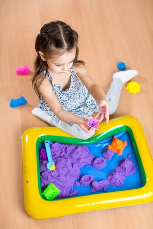 kids toys: Child girl moulds from kinetic sand in play room.  Preschool.