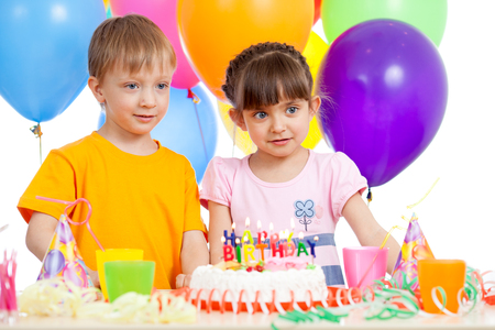 white party: Smiling kids boy and girl with party hat and a birthday cake isolated against white background