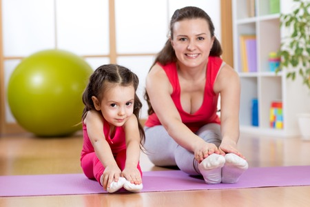 Healthy life. Woman and kid girl exercising together