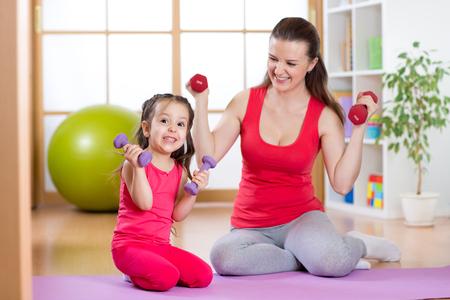levantar pesas: Mujer con el niño haga ejercicio divertido levantamiento de pesas, la maternidad saludable y el concepto de la paternidad