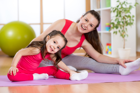 aerobic exercise: Portrait of kid girl and her mother doing gym exercise at home