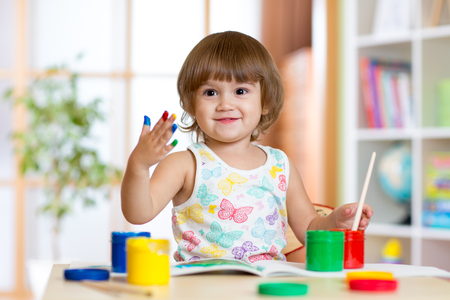Happy child girl with hand painted color paints sitting at table in nursery Stock Photo