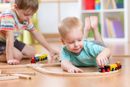 Children boys playing with wooden train set