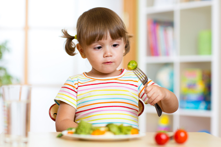 Little cute girl examines Brussels sprouts. Child with healthy food sitting at table in nursery