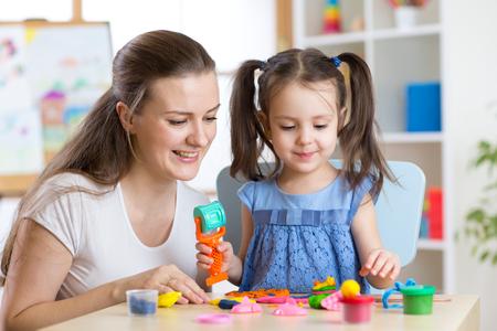 Moeder en jong meisje thuis gevormd uit klei en samen spelen. Concept van school of thuis onderwijs. Stockfoto