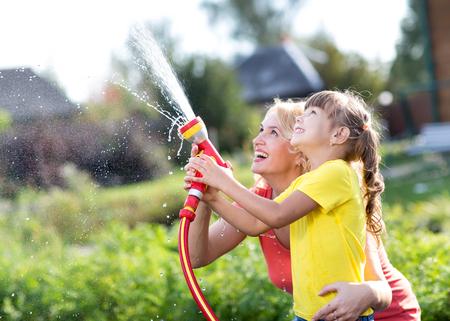 Portret van kleine tuinman meisje met moeder het water geven op gazon in de buurt van het huis Stockfoto