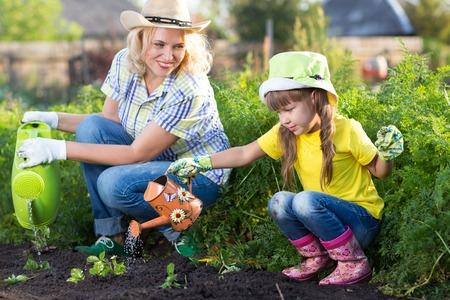 정원에서 엄마와 딸 아이 급수 식물.