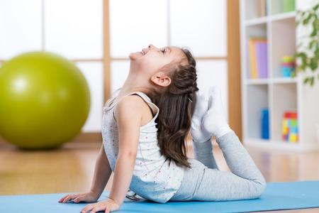 Barn flicka gör gymnastik på mattan hemma