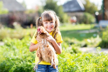 child portrait: Child little girl with hen near house outdoor