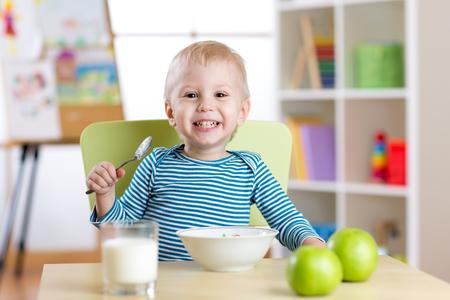 kid boy eating healthy food at home or kindergarten photo