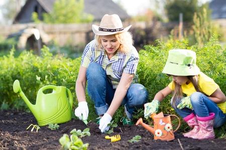 Vrouw met weinig dochter planten zaailingen in de tuin