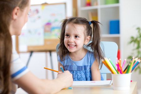 early education: Young woman or mother teaches child to pencil in daycare. Early education in preschool, kindergarten or home.