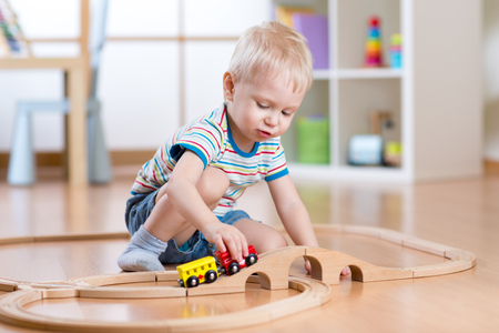 Child playing in his room with a toy train