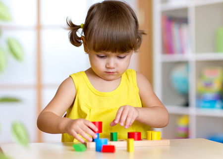 Little girl child kid playing with sorter toys in nursery