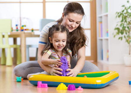 playschool: Child little girl and woman mould with kinetic sand in playschool or daycare Stock Photo