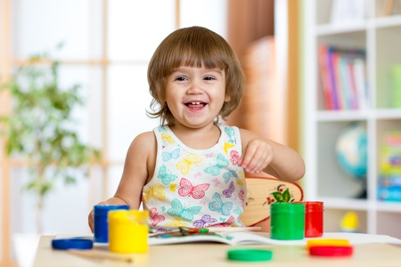 playschool: pretty child girl painting with colours in daycare or playschool Stock Photo