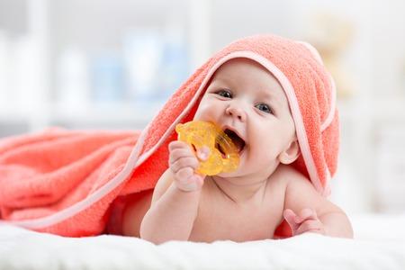 お風呂の後のフード付きタオルの下で口の中で歯がためにかわいい赤ちゃん 写真素材