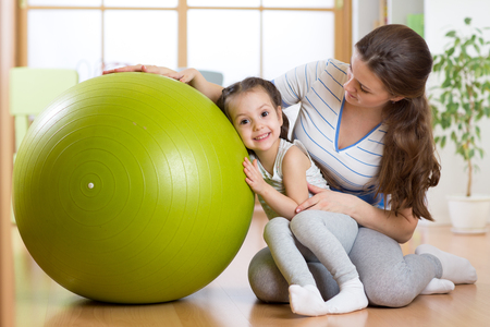 child ball: kid girl and mother with fitness ball indoor