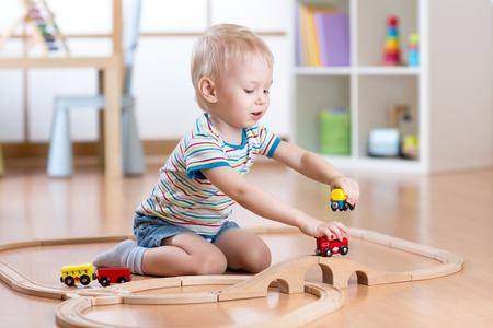 carritos de juguete: el ni�o jugando con juguetes de ferrocarril en interiores como en casa Foto de archivo