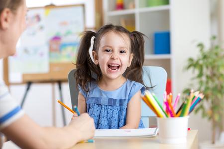 niños riendose: Profesor de sexo femenino y de la niña de risa, la pintura de los lápices de colores en su playtable