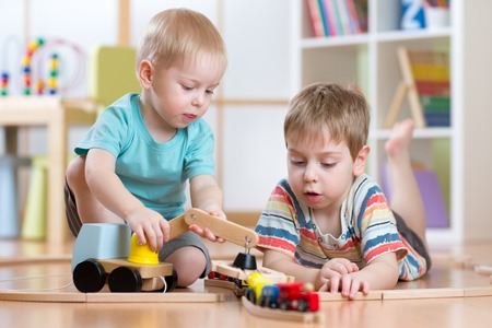 kids toys: children  boys playing rail road and car toys in playroom