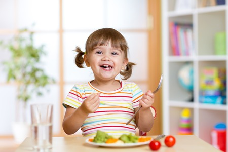 nutrition: Happy kid girl eating vegetables. Healthy nutrition for children