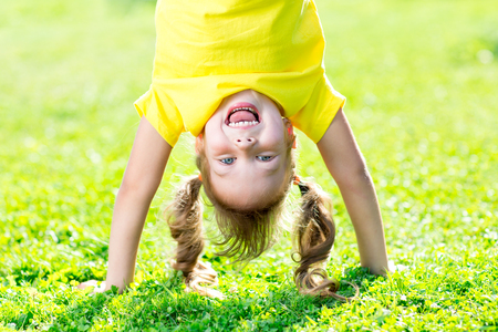 cute girl: Portraits of happy kid playing upside down outdoors in summertime standing on hands